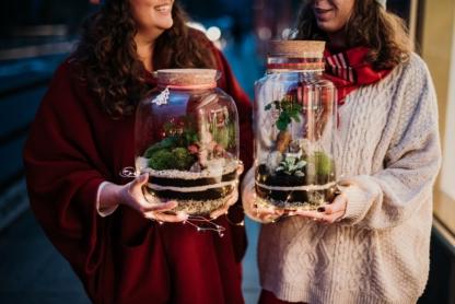 świąteczny las w słoiku bańka 32 cm i butla z drzewkiem bonsai trzymane w dłoniach